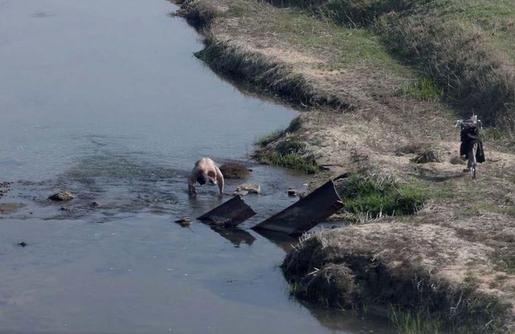 Mężczyzna kąpie się w rzece niedaleko miasta.