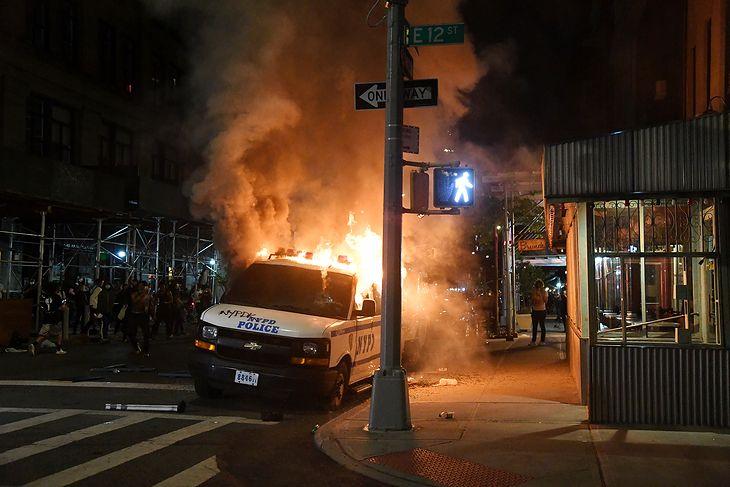 Nowy Jork. Strażacy gaszą płonący radiowóz.