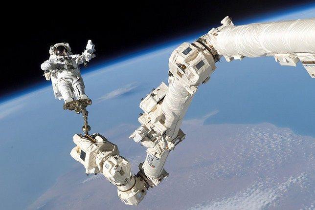 Astronauta Stephen Robinson na końcu znajdującego się w wyposażeniu ISS mechanicznego ramienia Canadarm2