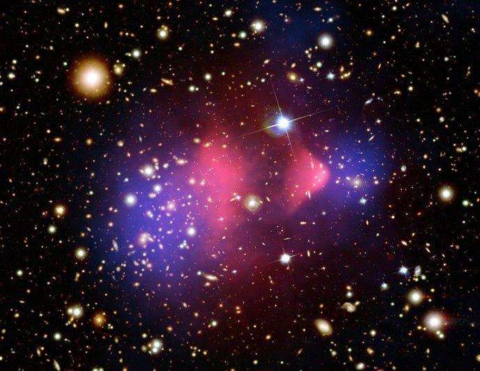 Gromada Pocisk. Na różowo  zaznaczono emitującą promieniowanie rentgenowskie materię barionową. Na  niebiesko - dwa ogromne skupiska ciemnej materii.