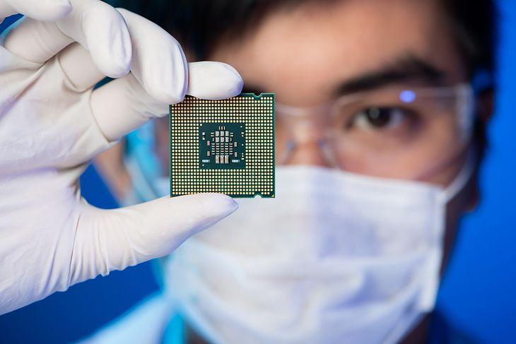 Zdjęcie Close-up portrait of a young computer engineer with microchip instead of his eye pochodzi z serwisu Shutterstock