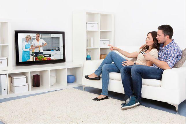 Zdjęcie pary przed telewizorem pochodzi z serwisu Shutterstock
