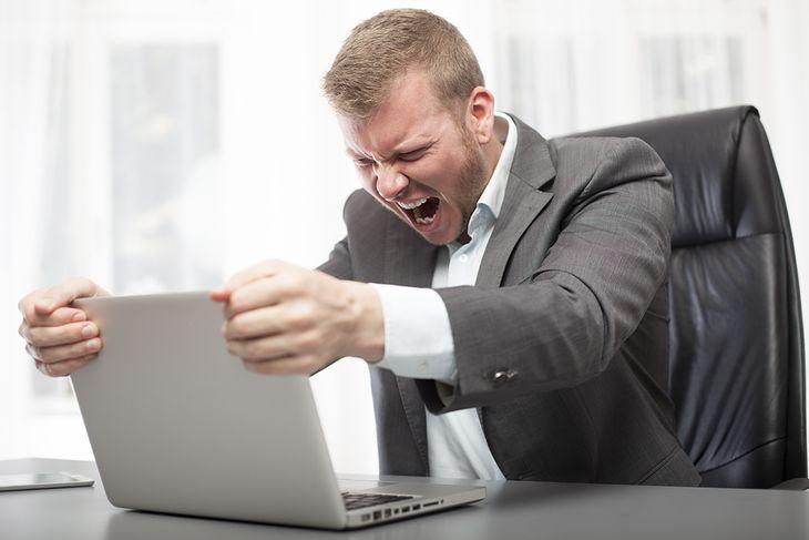 Zdjęcie mężczyzny wściekłego na laptopa pochodzi z serwisu Shutterstock