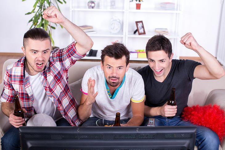 Zdjęcie kibiców przed telewizorem pochodzi z serwisu Shutterstock
