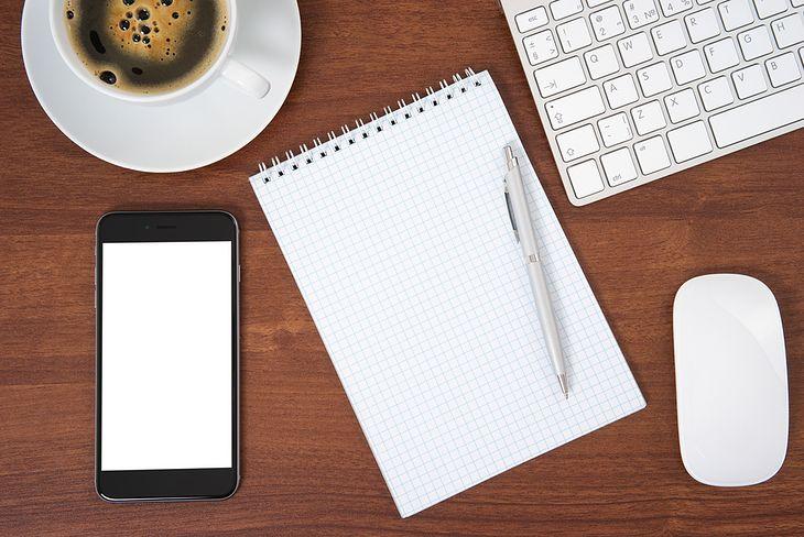 Zdjęcie Office table with keyboard, mouse and smartphone pochodzi z serwisu Shutterstock