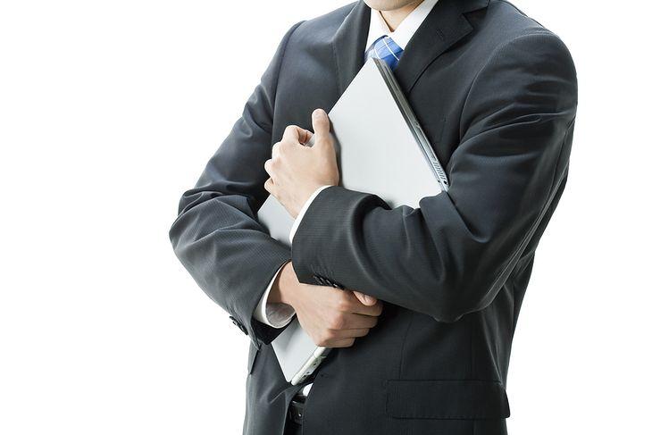 Zdjęcie Businessman holding laptop pochodzi z serwisu Shutterstock