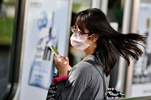Kobieta w masce z telefonem na dworcu ;) (fot. flickr/by colidio/lic. CC)