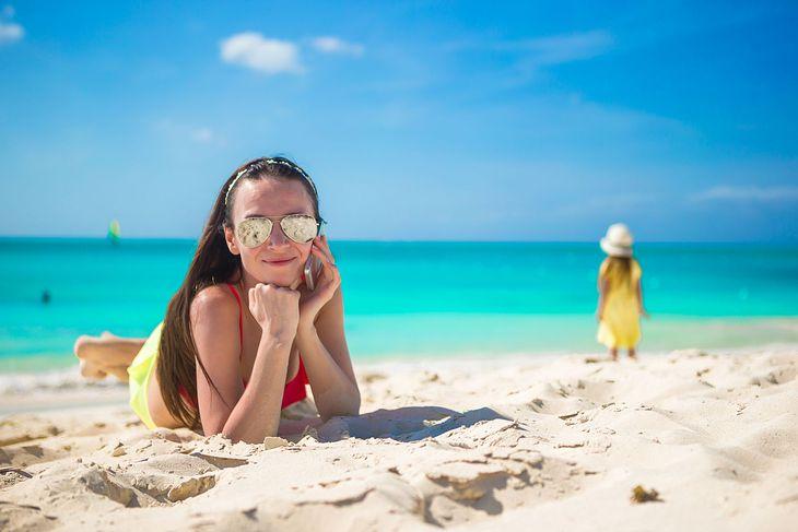 Kobieta rozmawiająca na wakacjach na plaży