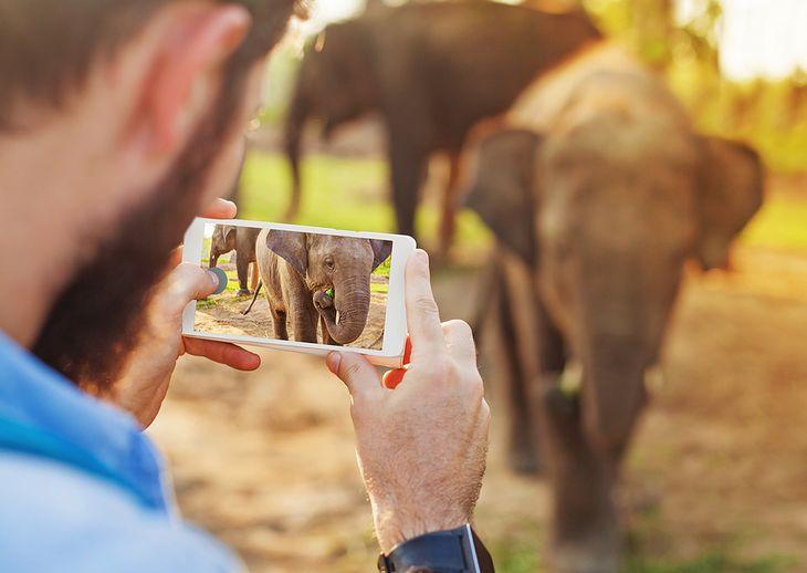 Mężczyzna robiący zdjęcie smartfonem