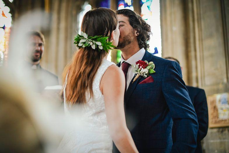 Ślub w kościele, para młoda się całuje