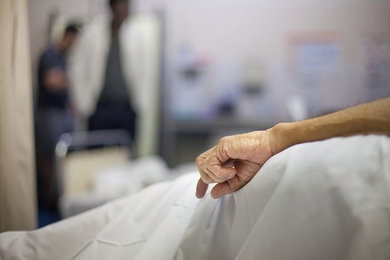 An old man's hand rests at his side in a hospital bed