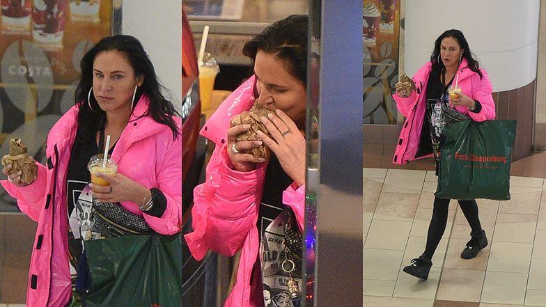 Naturalna Kayah w błyszczącej kurtce wcina kanapkę i popija sok pomarańczowy