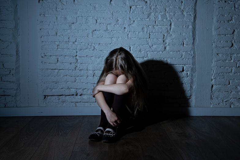 Sad desperate young girl suffering from bulling and harassment felling lonely, unhappy desperate and hopeless sitting against the wall, dark light. School isolation, abuse and bullying concept (Sad desperate young girl suffering from bulling and haras