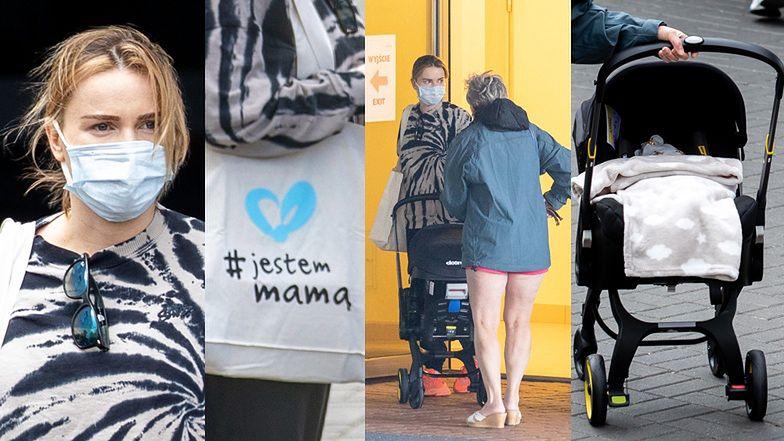 """Zamaseczkowana Maffashion wychodzi ze szpitala z dzieckiem i torbą z napisem """"jestem mamą"""""""