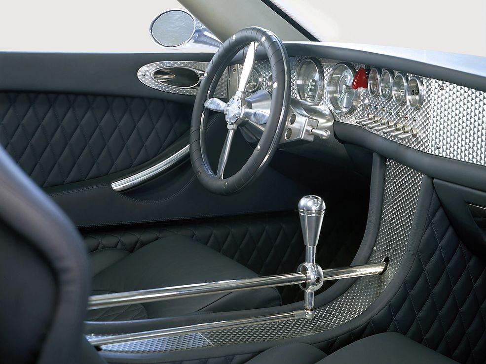 Spyker C8 Pierwszy przystanek nie będzie zbyt odległy, chyba że mówimy o inspiracjach designerów wnętrza. Ma ono bowiem odnosić się do aut z pierwszych dekad XX wieku. A C8 pojawił się przecież na początku XXI wieku. Jego wnętrze jest jednak nie mniej osobliwe niż nadwozie. Są tylko dwa wyjścia – albo go pokochasz, albo go znienawidzisz.  Misterne wykończenia, wszechobecny chrom, czy kierownica z ramionami w kształcie śmigieł przytłaczają wręcz pasażerów. Wisienką na torcie jest jednak niczym nieosłonięty aluminiowy mechanizm zmiany przełożeń, zawieszony nad środkowym tunelem. No i ta pikowana skóra. Mieli Holendrzy fantazję. Sportowe aspiracje też nie są na pokaz, mamy tu zawieszenie wzorowane na Formule 1, regulację rozdziału siły hamowania czy podrasowane V8 z Audi.