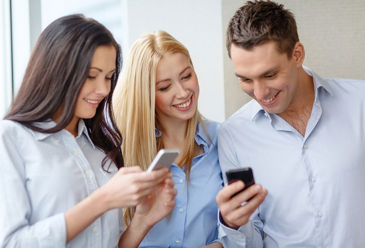 Smiling business team with smartphones